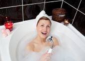Cheerful Young Woman Singing In A Bubble Bath