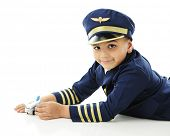 A happy elementary boy playing with a toy commercial airplane on the floor while wearing a blue and gold pilot uniform.  Isolated on white with space on the left for your text.