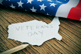 picture of veterans  - a piece of paper in the shape of United States with the word Veterans Day on a wooden background with the flag of the United States in the background - JPG