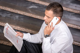 pic of unemployed people  - Young unemployed man is looking for a job in the newspaper and phone sitting on the stairs - JPG