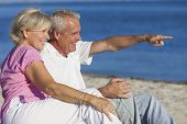 stock photo of couple sitting beach  - Senior man and woman couple sitting on a deserted beach pointing to the sea - JPG