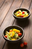 picture of sweet-corn  - Two bowls of baked vegetables of sweet corn zucchini and cherry tomato seasoned with thyme photographed on dark wood with natural light  - JPG