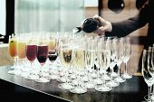 stock photo of bartender  - Bartender is pouring sparkling wine in glasses - JPG
