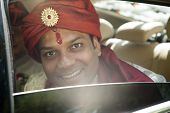image of traditional attire  - Handsome young Hindu Groom smiling out of car window in traditional attire