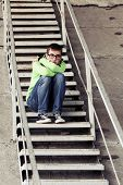 foto of depressed teen  - Teen boy in depression sitting on the steps  - JPG