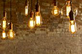 stock photo of decorative  - Decorative antique edison style light bulbs against brick wall background - JPG