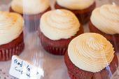 pic of red velvet cake  - Fresh red velvet cupcakes with cream cheese frosting in display case - JPG