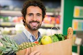 picture of supermarket  - Smiling man shopping in a supermarket - JPG