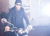 picture of chopper  - Bearded man posing with his shiny stylish chopper - JPG