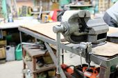 picture of workbench  - The image of a old vice on a metal workbench - JPG