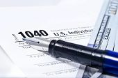 image of pen  - Tax form 1040 on a gray background blue pen and 100 dollar bills out of focus - JPG