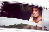 stock photo of limousine  - Beautiful blonde drinking champagne limousine on a sunny day - JPG