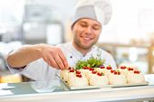stock photo of confectioners  - Handsome confectioner in uniform decorating cakes with currant - JPG