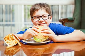picture of tween  - Happy blond tween enjoying a hamburger and french fries at home - JPG