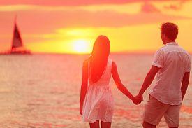 foto of sea life  - Honeymoon couple romantic in love holding hands at beach sunset - JPG
