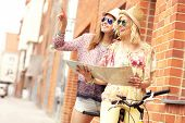 image of tandem bicycle  - A picture of two girl friends using a map and riding a tandem bicycle in the city - JPG