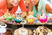 image of ice cream sundaes  - Young female customers or friends with sorts of ice cream for cornets and cones and sundaes in parlor - JPG