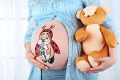 foto of  belly  - Beautiful young pregnant with baby toy  and picture on her belly - JPG