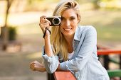stock photo of natural blonde  - beautiful blond woman taking photos in the nature - JPG
