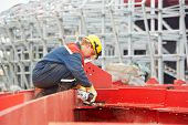 image of welding  - builder worker in safety protective equipment smothing out welded joint at metal construction frame by grinding machine - JPG