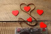 stock photo of heart sounds  - Audio cassette with magnetic tape in shape of heart on wooden background - JPG