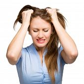 stock photo of pulling hair  - Portrait of a desperate young businesswoman pulling her hair - JPG