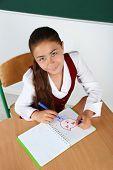 foto of schoolgirls  - Beautiful little schoolgirl in classroom and draws in notebook - JPG