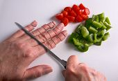 pic of mayhem  - A human hand is being chopped with a knife on a cutting board - JPG