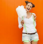 stock photo of candy cotton  - Beautiful fashionable girl with cotton candy posing nex to the orange wall - JPG