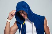 foto of hoods  - Handsome fitness man in hood looking at camera over gray background - JPG