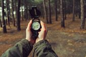 stock photo of pov  - Hiker woman holding a compass in the forest - JPG