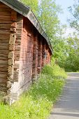 stock photo of red barn  - Red traditional wooden old barn and country road - JPG