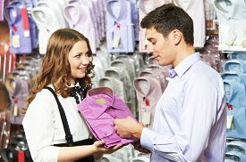 picture of apparel  - Young man choosing shirt and necktie during apparel shopping at clothing store - JPG