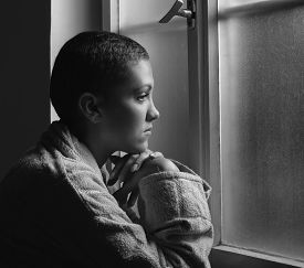picture of hospital gown  - Young cancer patient standing in front of hospital window - JPG