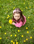 Small Girl Picking Up Flowers In The Spring Meadow