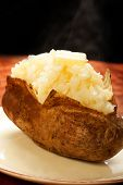 image of baked potato  - Steamy baked potato with pat of butter - JPG