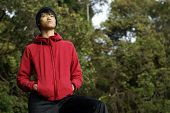 Asian man looking up in red sweater
