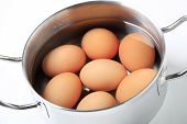 picture of boiling water  - Brown eggs in water in a metal pot - JPG