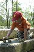 picture of team building  - little boy up on a stone playing with sand - JPG