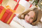 Pretty blonde hair girl looking at small red gift with gold ribbon. Christmas tree and bunch of pres
