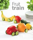 Train made of various fruit on white table cloth