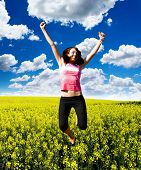 Happy girl jumping in Bright Canola Field