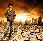 Male standing on cracked earth in front of a city