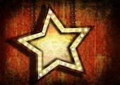 A grungy star sign with marquee lights hanging by chains. Grunge velvet wallpaper in the background.