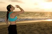 Woman drinking water after exercising on the beach