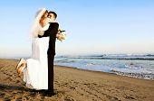 stock photo of wedding couple  - Couple at their beach wedding - JPG