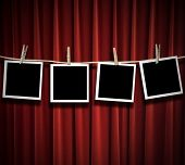 Blank photos hanging from a clothes line against a red curtain