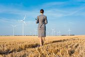 Investor in wind turbines with computer evaluating her investment on site poster