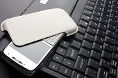 modern mobile phone over laptop keyboard