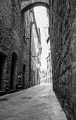 Rough Stone Walls In Dark Narrow Laneway Lined By High Stone Buildings Leading Bright Street Ahead. poster